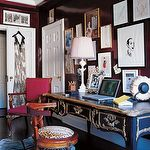 dens/libraries/offices - gloosy brown walls lacquer Elle Miles Redd zebra brown ornate modern zebra cowhide rug eclectic art gallery antique desk red chair and white lamp.