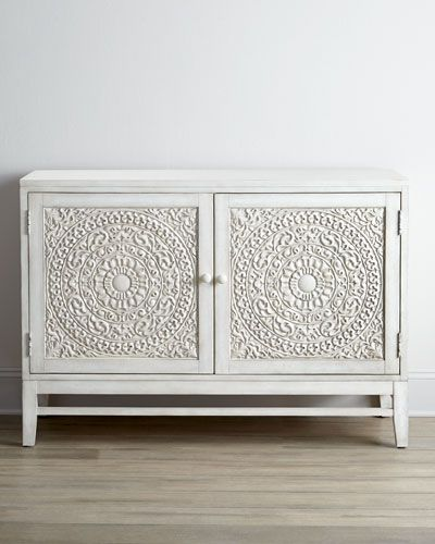Decorative chest ideal for TV or other electronics display. Made of hardwood solids, laminated lumber, veneers, and resin. Carved door fronts. Hand-painted antiqued-white finish. Two doors and one adj