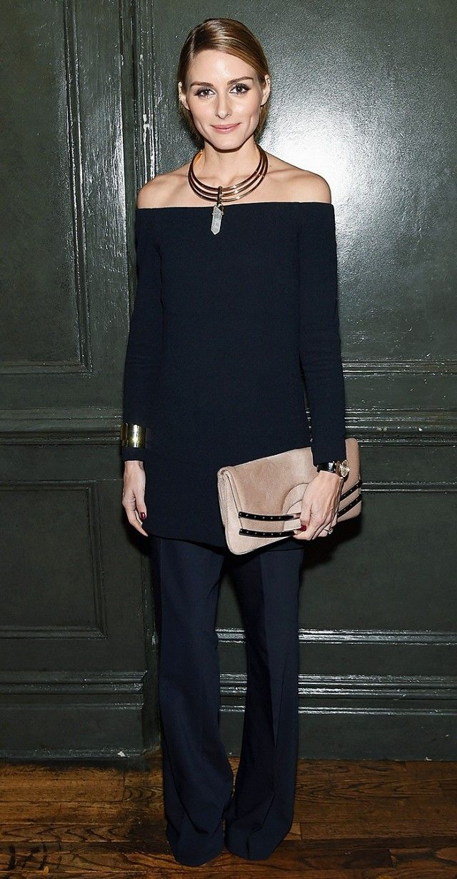 Olivia Palermo wears an off-the-shoulder top with navy blue trousers, a neutral clutch, and a statement necklace