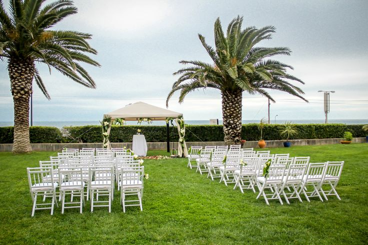 White Canopy and white wooden chairs - destination wedding celebration by the Sea . Photo by Portugal Wedding Photographer #destinationweddingsinportigal #weddingceremonyportugal #portugalweddingphotographer