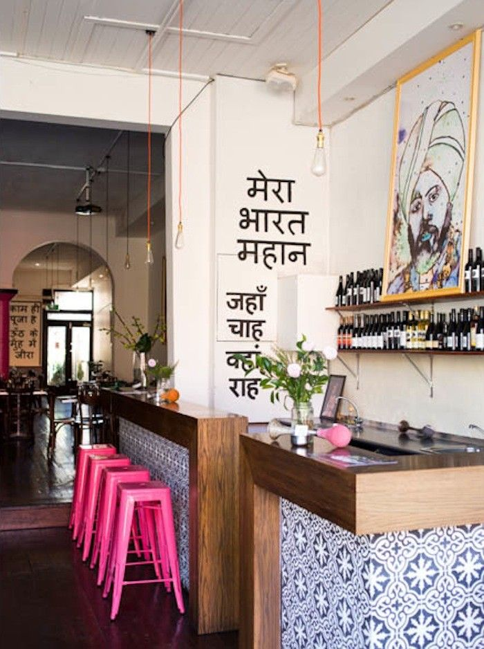 Indian restaurant in Melbourne Australia Hot pink Tolix stools stand out against the bar's blue and white tiles