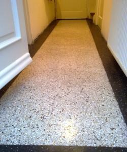 Granito of terrazzo vloer: een karakteristieke lichte vloer met rondom een zwarte band welke met een ronde kant een stukje tegen de muur opstaat.