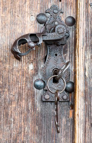 An old metal handle and keys on a wooden door. Latch style door handles are more practical than knobs to me as they're easier to open with wet hands or arms full of grocerries. This one is beautifully ornate but not overly so.