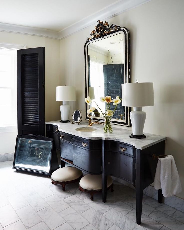 Black and white bathroom with marble counter and antique French mirror,