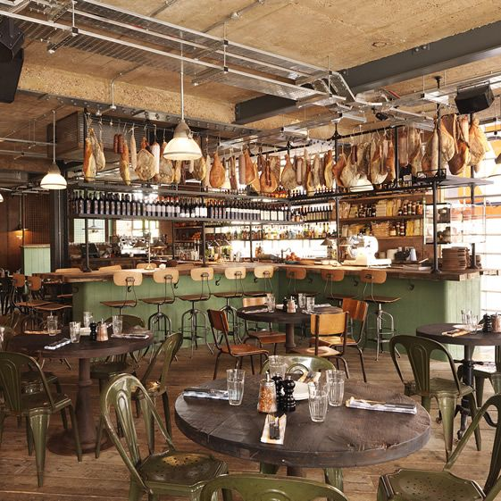 Ham hocks and various other tasty-looking animal appendages hang tantalizingly from the ceiling structures, and a wall of logs alludes to the wood-fired oven which makes the culinary magic happen...