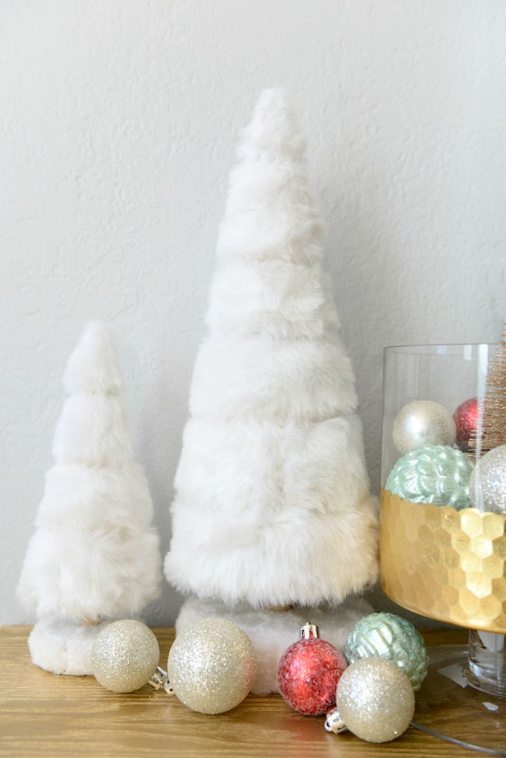 Give an entryway or tabletop easy, whimsical Christmas decor. Hurricane glasses filled with ornaments look merry and bright positioned by a pair of faux fur trees. Click this pin to get more last-minute decorating ideas from Hello Splendid.