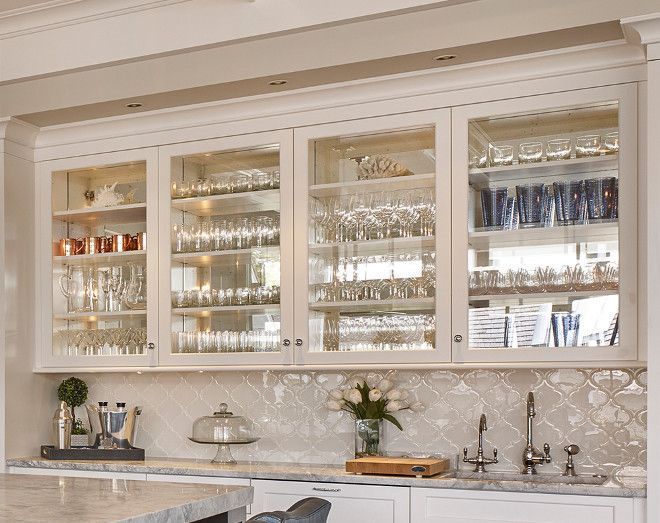 The kitchen bar features glass cabinet doors with mirrored back and white Arabesque backsplash tile