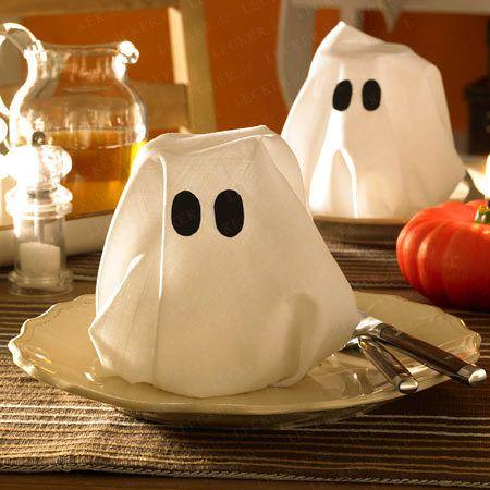 1. Eine weiße Serviette ganz auseinanderfalten und über ein umgedrehtes Glas legen, die Ecken der Serviette in das Glas stecken. 2. Den Geist zusammen mit Halloween-Konfetti auf einen Teller stellen.