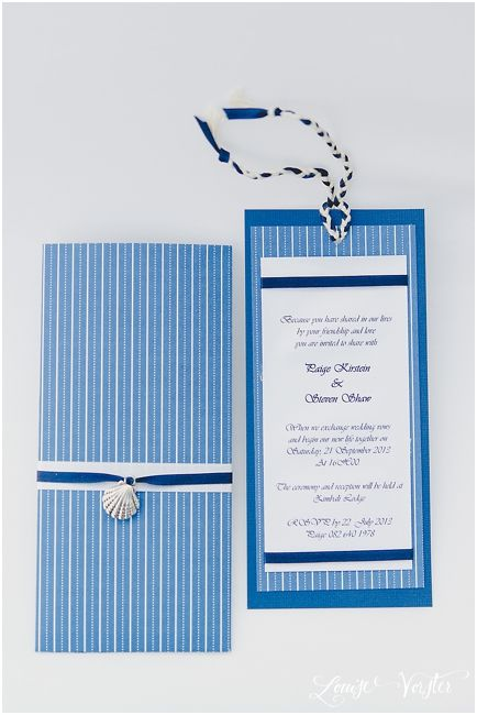 Blue and white invitation and folder with blue and white ribbon with silver shell charm