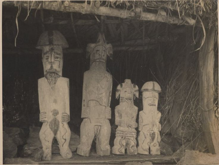 Nigeria, upright Ibo wooden sculpture [carved wood?] set amongst trees. Another lying at ground, small group at rear left.