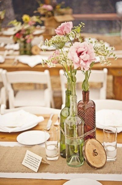 Woodland themed centerpiece, with flowers in a wine bottle (can also use a jar?)