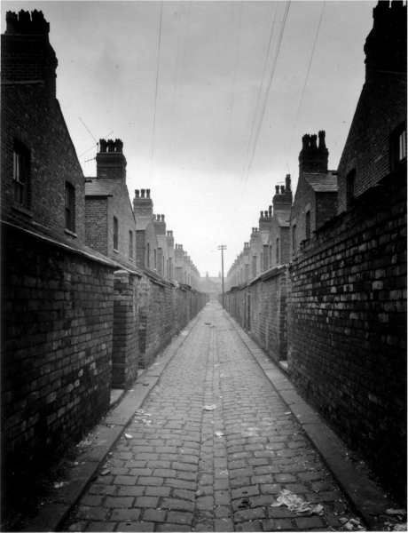 Manchester - back entry (or ginnel) between rows of terraced houses probably sometime in 1960s