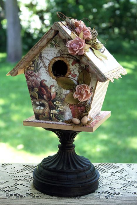 Gorgeously decorated birdhouse using bird and flower decoupage paper. The tiny little eggs and flowers give it a charming touch as well as standing the birdhouse on a black pedestal.