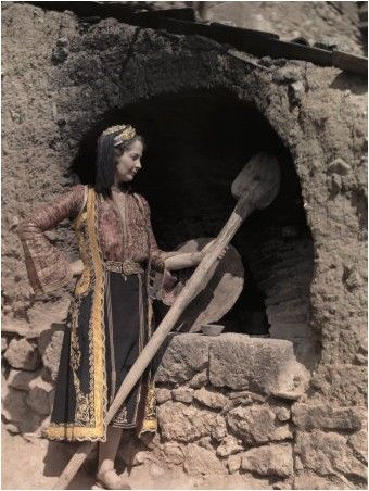 Actress in Costume of Epirus Stands at an Outdoor Oven National Geographic's Greece in Color from the 1920s Photographer: Maynard Owen Williams in the 1920s