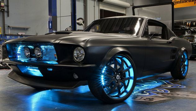 West Coast Customs took a 2012 Ford Mustang and retrofitted it with a 1967 Mustang fastback replica body. They painted the car matte black, and decked it out with neon blue lights in the grill and around the rims.