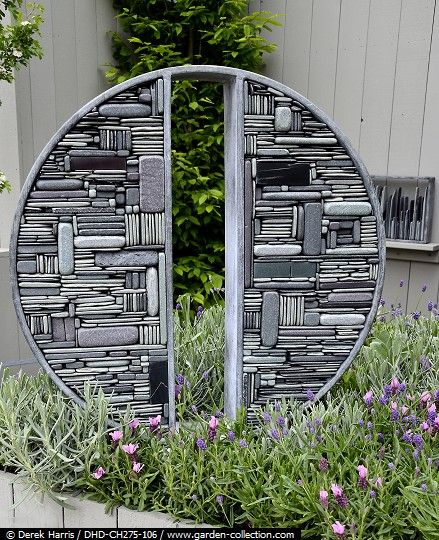 contemporary decorative garden feature made of stones or driftwood use an old wheel for outside