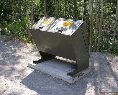 You see these bear-safe garbage cans in whole western Canada. To open it a lever in the handle has to be pushed.