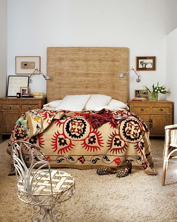 Natural-neutral bedroom; Suzani coverlet is tan/gold base w/ black and red embroidery; grass material for headboard; vintage French Provincial style white wrought iron bistro/garden chair; room by Rocio Monasterio- love with a darker wall color scheme