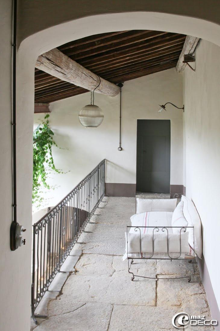Dans la coursive de La Maison d'Ulysse, maison d'hôtes à Baron dans le Gard, un vieux lit d'enfant en fer se transforme en canapé