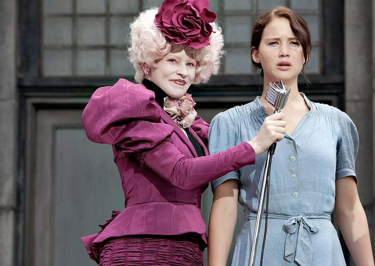 Effie Trinket's theatrical style perfectly represents the over-indulgent ruling class of Panem in The Hunger Games series. Click through to see every garish outfit she has worn.   (Photos: Lionsgate; additional reporting by Giana Mucci)