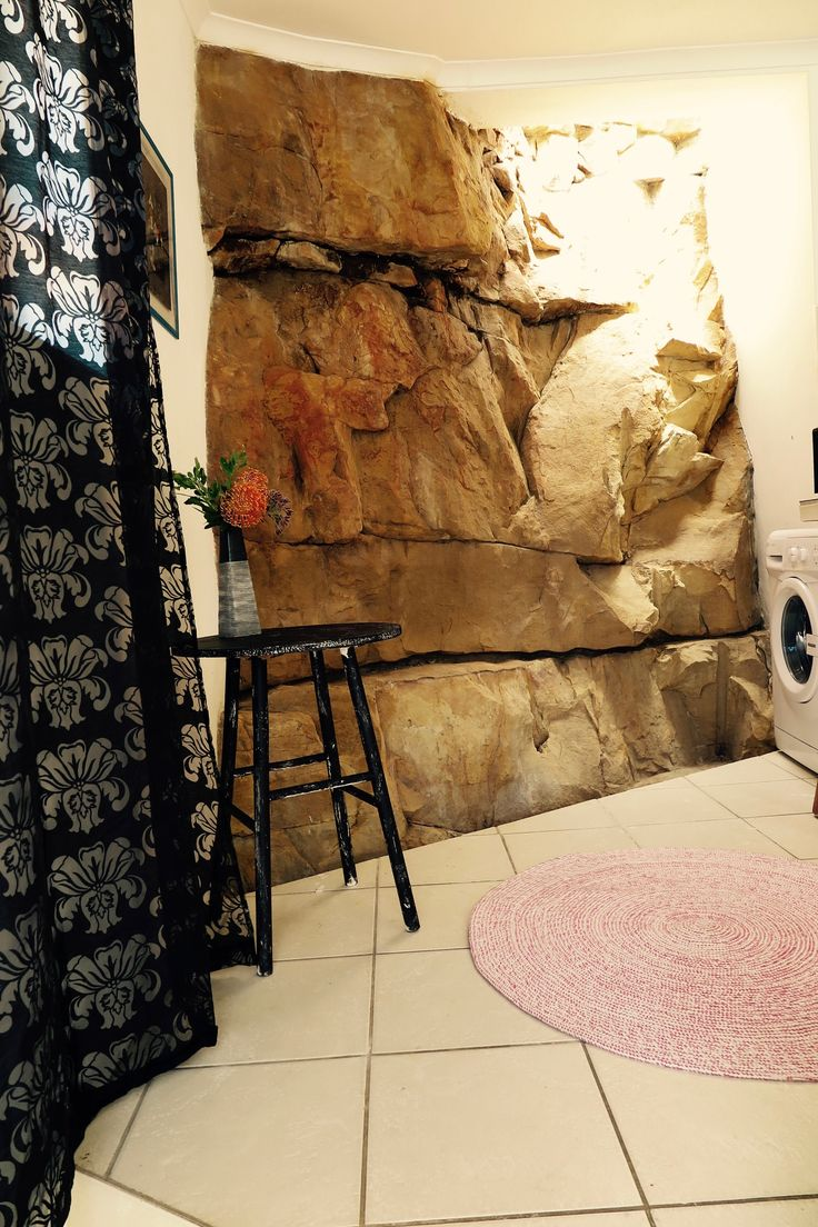 The house is built onto the side of the mountain, and the natural rock is a feature in the house