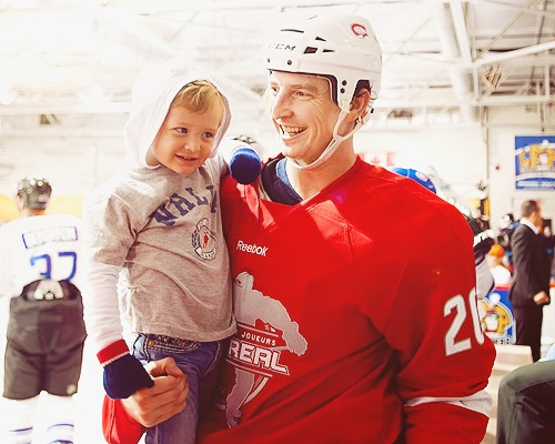 Montreal Canadiens' Colby Armstrong with his son Cruise at the end of the first period of a charity hockey game