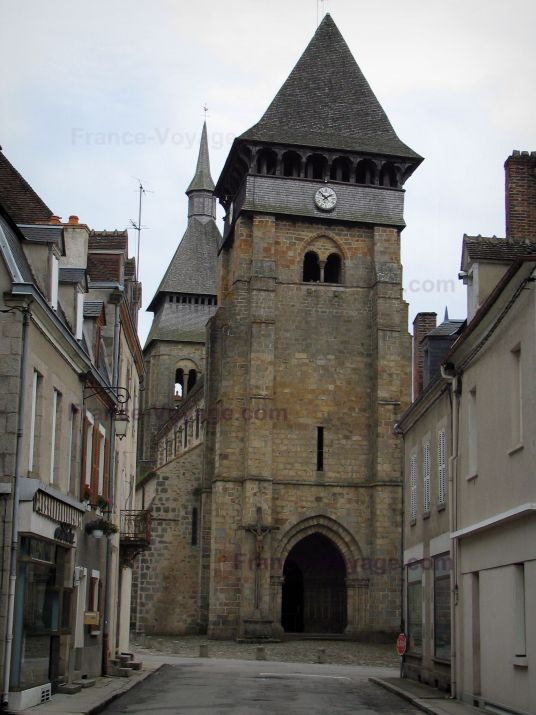 Chambon-sur-Voueize: Sainte-Valérie abbey church of Romanesque Limousin style with its two bell towers, street and houses of the city - France-Voyage.com