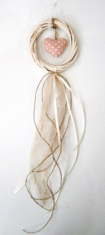 Mπομπονιέρα βάπτισης κρεμαστή με λευκό στεφανάκι από πλεκτά κλαδιά από το οποίο κρέμεται υφασμάτινη πουά καρδούλα στο χρώμα του σάπιου μήλου. Στις κορδέλες και τα σχοινάκια που κρέμονται τοποθετούνται 3 μεγάλα κουφέτα αμυγδάλου  Υλικό: κλαδιά, ύφασμα, σχοινί, κορδέλες
