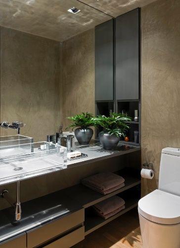 O mesmo cimento queimado que reveste os ambientes sociais aparece no banheiro, que tem ainda armário preto, bancada e prateleiras em laca cinza e cuba de acrílico. O projeto de reforma do Loft Vila Leopoldina leva a assinatura do arquiteto Diego Revollo