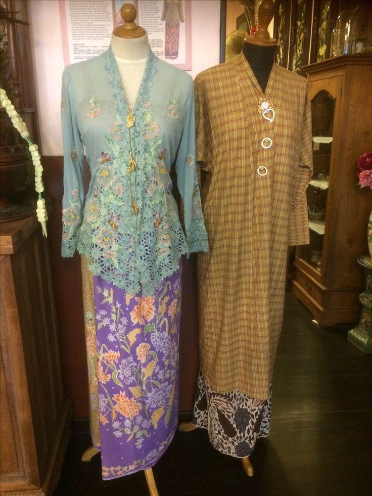 Baju panjang and sarong Kebaya @ Kim Choo Museum. The Peranakan attire has Chinese and Malay origins. The Nyonya's attire consists of a kebaya with embroidered edges, three kerongsangs (brooches) and a sarong.