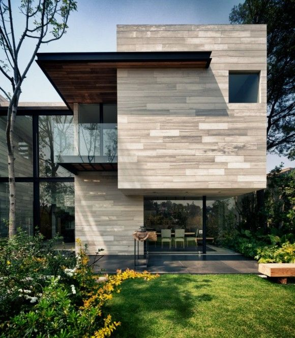 love the wood panel look of this concrete house, and how the black framing ties in with the paving