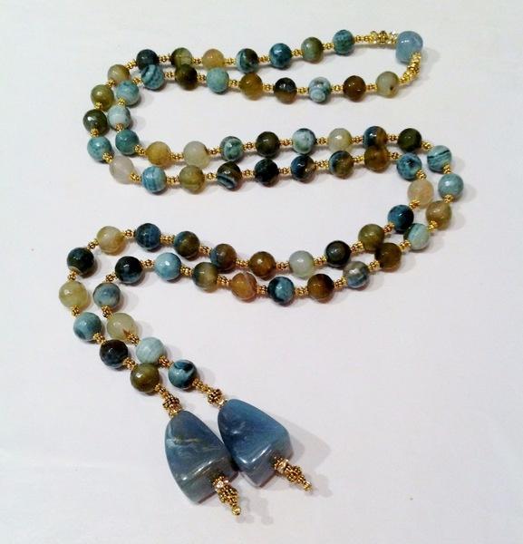 Sofisticata collana a laccio con un unico lunghissimo filo di corniola, angelite e ambra e due pendenti finali all'estremità in resina.  La collana...