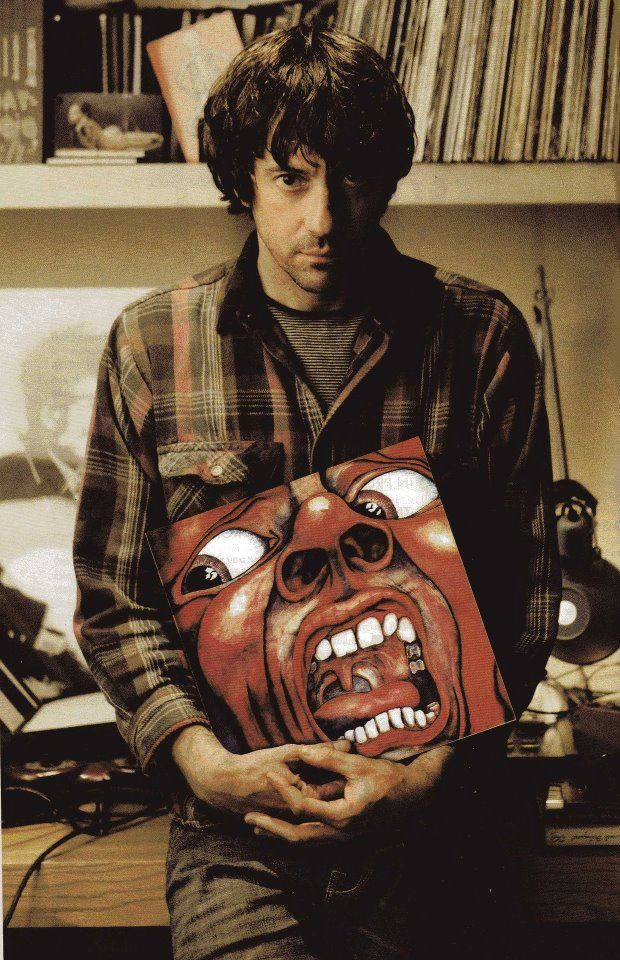 Graham Coxon holding a great album, 'In the Court of the Crimson King' by King Crimson.