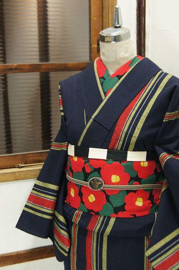 濃紺色地に淡黄色と赤で織り出された大胆な縞模様が小粋なウールの単着物です。