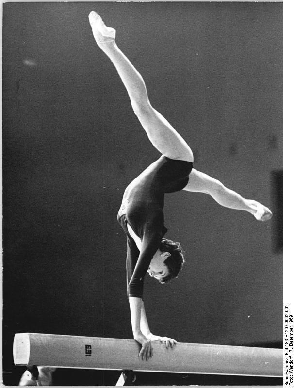 Gymnast Marianne Noack performing split leg handstand on balance beam  (1969).