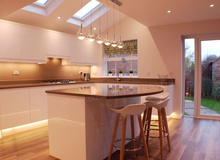 Contemporary white high gloss handless kitchen design, with Quartz tops and family friendly design