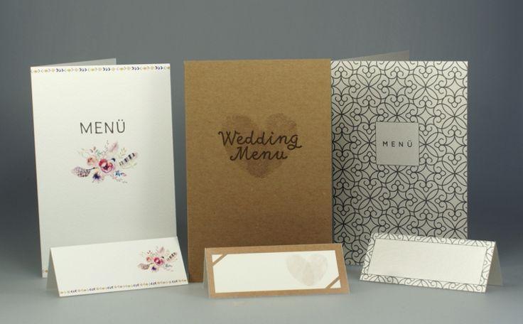 Drei Menükarten mit passenden Tischkarten für die Hochzeitsfeier. Die erste mit romantischem Blumenmotiv, die zweite aus trendigem Kraftkarton mit Herz aus Fingerabdrücken und die dritte mit Ornament in anthrazit