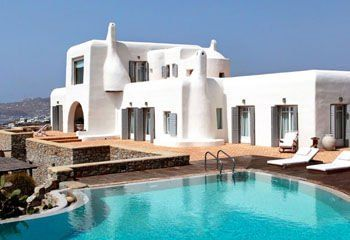 """This is a stylish 7 bedroom private property is in the exclusive area of Agios Lazaros on the southwestern side of Mykonos. The villa enjoys a privileged position with breathtaking views that extend over the bay of Ornos, the island of Delos and the memorable Mykonian sunsets. The location is further enhanced by the vicinity to Psarou beach, the """"in"""" spot on the island, and the short distance from Mykonos Town, just a 5-minute drive away."""