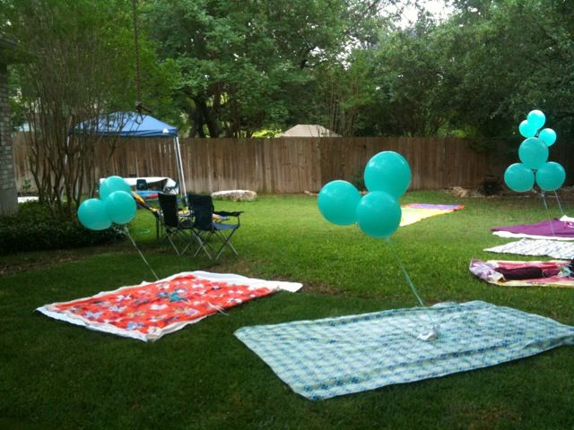 Balloons tied to teddy bears, on picnic blankets.