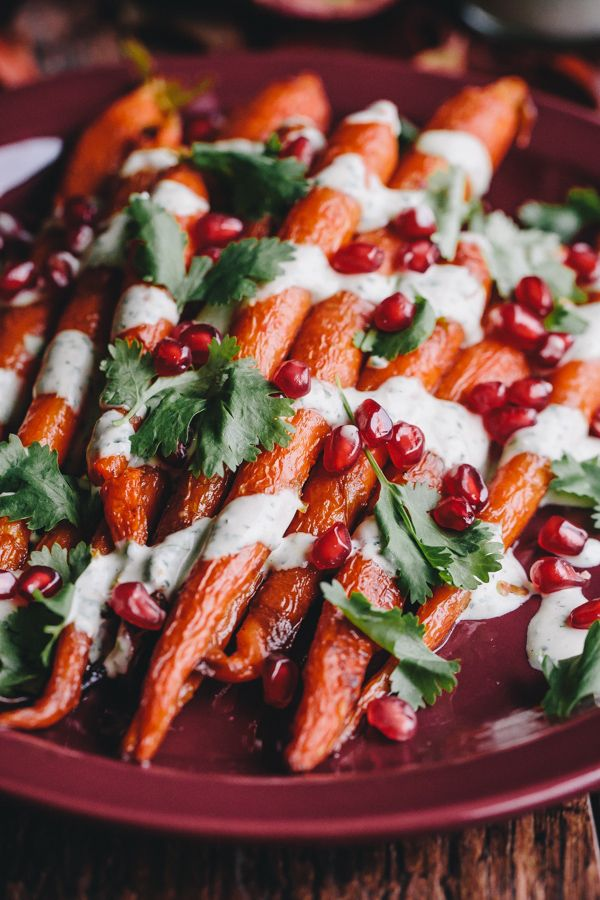 Beautifully festive roasted carrots with green tahini sauce and pomegranate arils. This vegan and gluten-free dish makes a great fall or winter side dish!