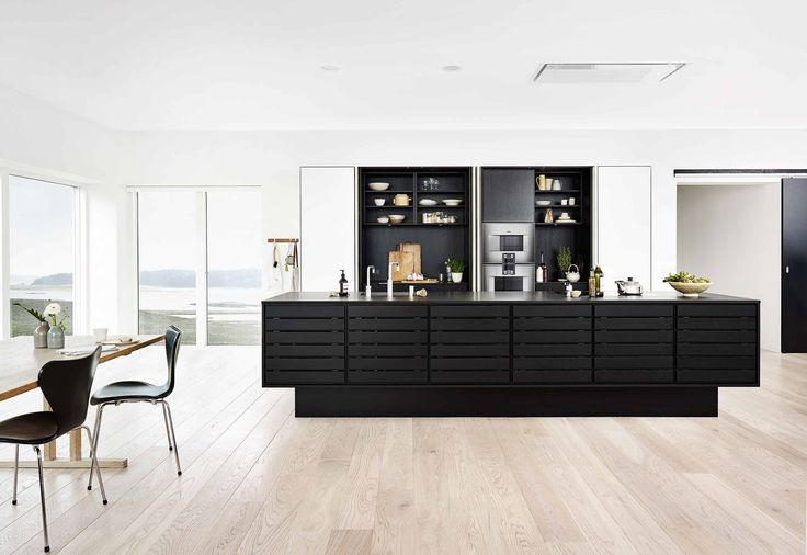 Form 1 // Black oak. A floating black kitchen island is the centre of a spacious kitchen where the appliances are elegantly hidden behind pocket doors. A combination of form and function that creates not just a great kitchen, but also a timeless piece of furniture.