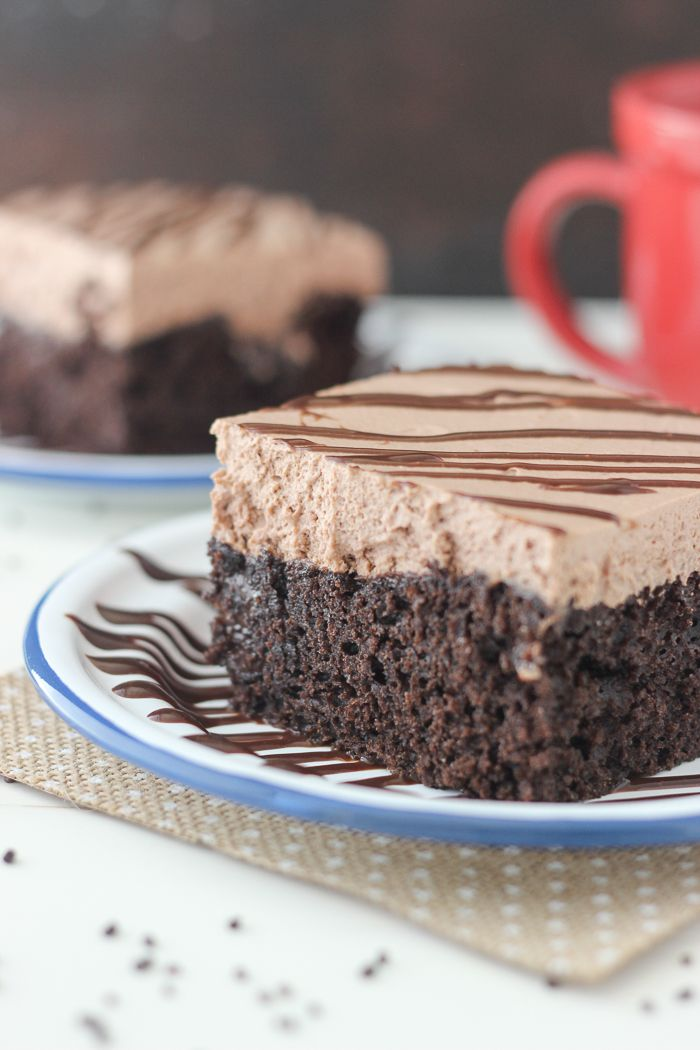 This Hot Chocolate Poke Cake is a rich chocolate cake with hot fudge glaze and hot chocolate whipped cream.