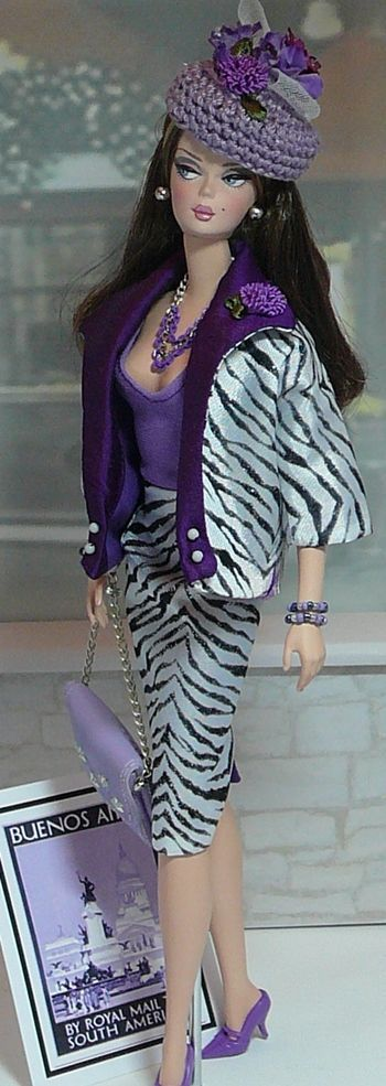 Donna Doll Designs  Around the World - Buenos Aires  This chic ensemble 2-pc travel suit is cut from black&white zebra print silkie fabric . Both skirt and jacket are fully lined and skirt has back snap closure. Worn with the suit is a lavender knit bodysuit. Accessories include a lavender leatherette handbag with silver tone metallic accents. The lavender cotton crochet pillbox hat is embellished with silk floral accents. Jewelry is a triple chain necklace, a pair of silver ball earrings