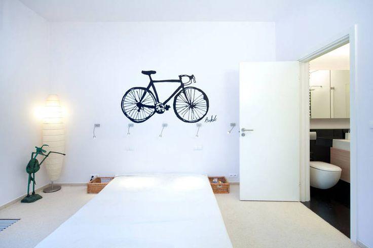 Ten minimalistyczny wystrój młodzieżowej sypialni zawiera kilka ciekawych pomysłów. Przy materacu oświetlonym rzędem reflektorów zamiast stolików ustawiono płytkie rattanowe kosze na drobiazgi. W roli ozdoby wezgłowia występuje wyrazista czarna naklejka.
