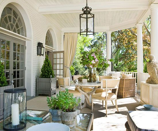 Spacious Sanctuary - This large outdoor porch provides the perfect summertime entertaining area. The grand space was split into two seating areas, one with a dining table and one with a sofa and chairs. A palette of soft neutrals unifies both areas. Outdoor drapes can be drawn to diffuse bright sunlight to ensure diners don't need to squint their way through a meal.