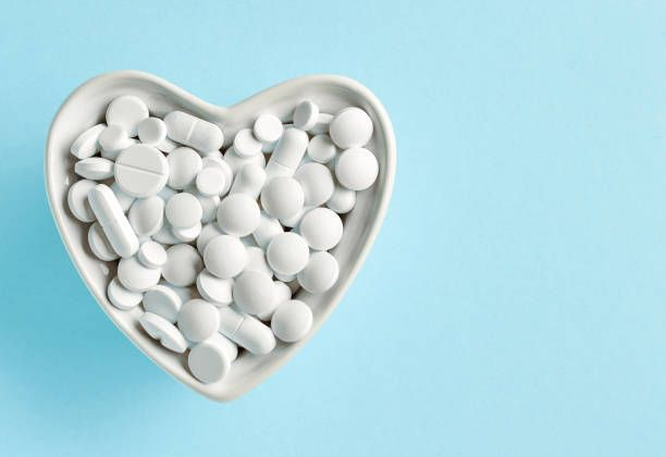 heart shaped bowl of white pills