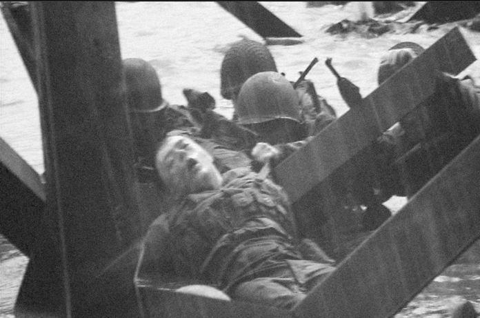 Omaha Beach - Des soldats essaient de soustraire un blessé aux tirs allemands. (Collection privée) (gewonde soldaat - water - tussen obstakels van het strand)