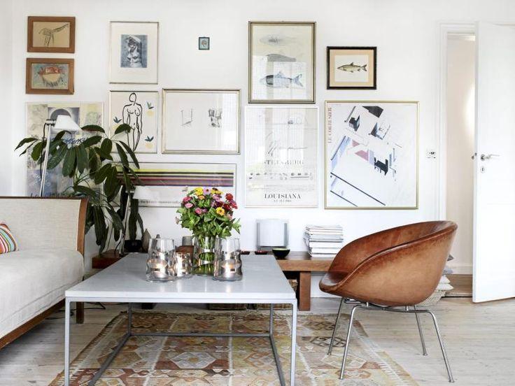 """Dette er en stillig stue med retroelementer. En hel vegg er fylt opp med bilder, slik at rommets andre vegger kan holdes rene. På denne måten unngår man å få for mye """"rot""""."""
