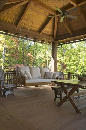 Covered deck with cathedral ceiling, swing, and ceiling fan.