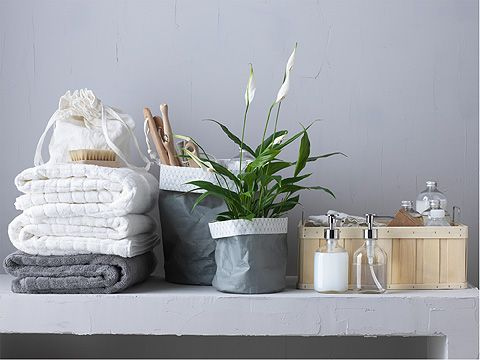 En stak hvide og grå håndklæder ved siden af 2 urtepotteskjulere, sæbepumper og en kurv.